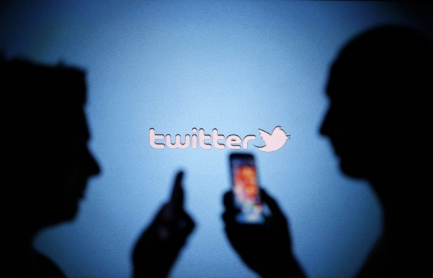 Men are silhouetted against a video screen with a Twitter logo in this photo illustration file photo taken in Zenica