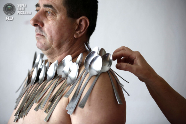 Buljubasic, 56, stands as his wife Senija puts cutlery on his body in Srebrenik
