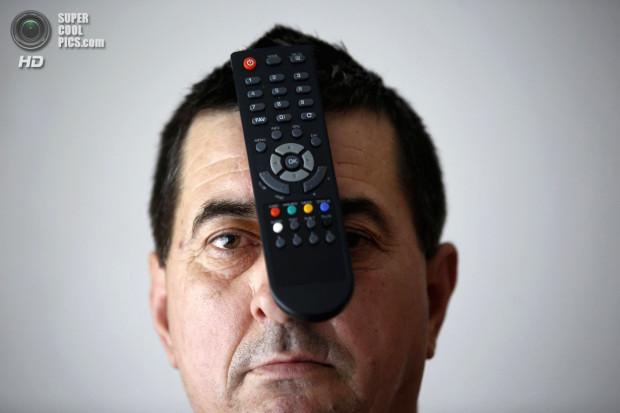 Buljubasic, 56, poses with a TV remote on his head in Srebrenik