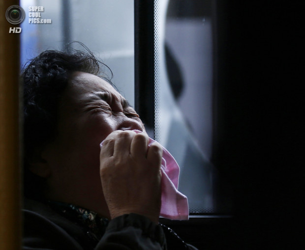 A family member of a passenger onboard Malaysia Airlines Flight MH370 cries on a bus before heading to the Malaysian embassy, outside Lido Hotel in Beijing