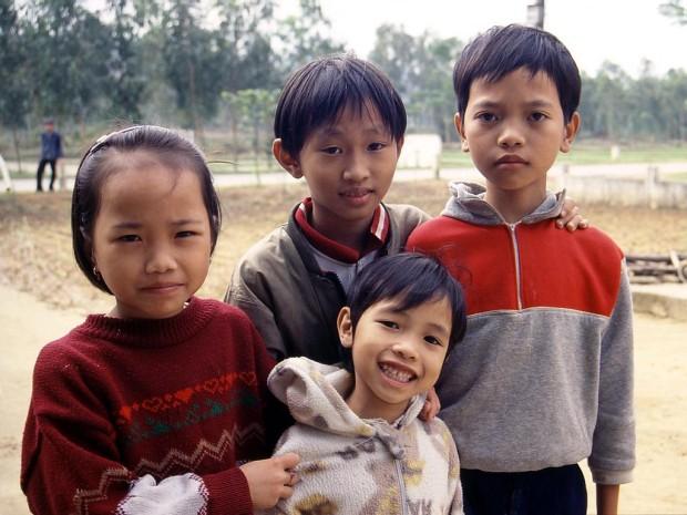 Вьетнамские дети переправляются через реку в полиэтиленовых мешках