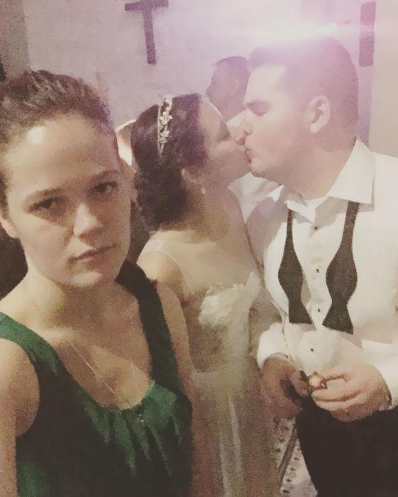 Одинокая девушка делает селфи на фоне влюбленных пар
