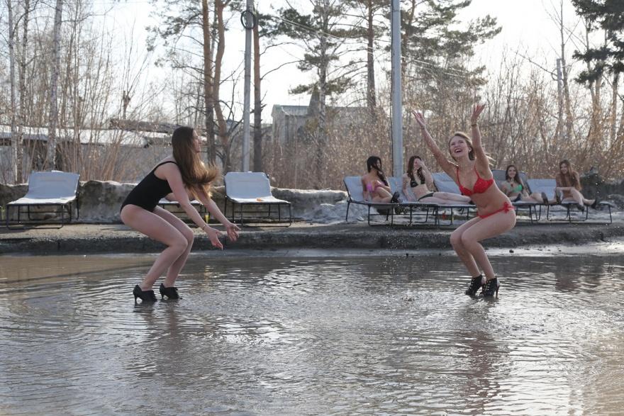 В Новосибирске девушки в купальниках загорали на берегу большой лужи (8 фото)