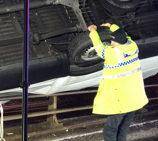 Полицейский удерживал автомобиль, зависший на краю моста (2 фото)