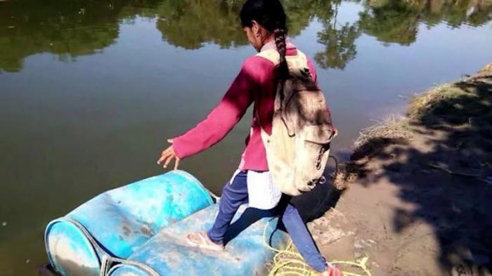 Индийские школьники вынуждены пересекать реку на пластиковых бочках (6 фото)