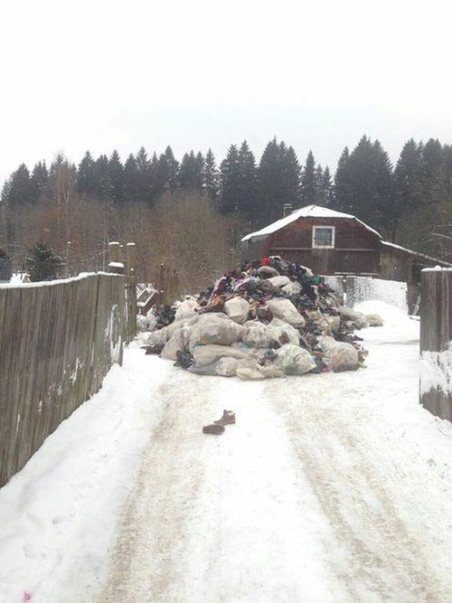 В Ленинградской области у одного из домов высыпали гору одежды (3 фото)